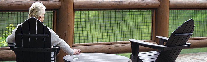 woman sitting in Adirondack chair on the deck at Fullersburg Woods Nature Education Center