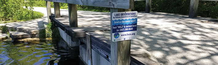 lake observation sign next to a gauge in the water